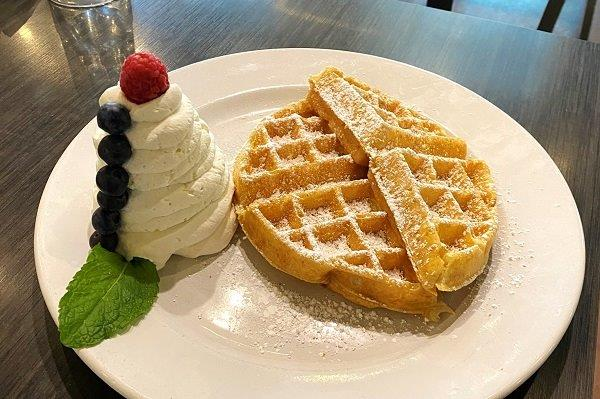 plate with belgian waffles and cream beside them