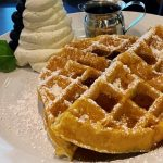 waffles on a plate with cream beside