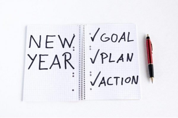 notebook with sign new year on the left and checklist with terms goal, plan and action on the wright side